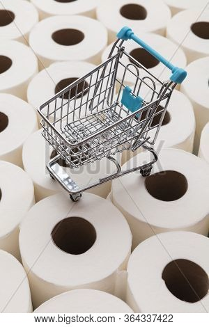 Supermarket Shopping Trolly On A Background Of Toilet Paper Rolls