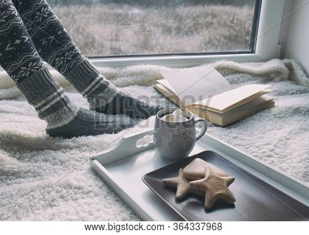 Hot chocolate and gingerbread and woman reading book by the window in the background