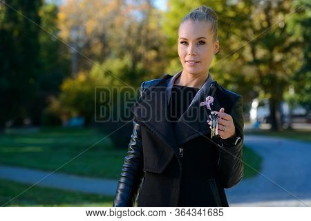Young Beautiful Woman Holding Keys Along The Path In The Park