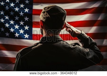 Memorial Day. A Uniformed Soldier Salutes Against The Background Of The American Flag. Rear View. Da