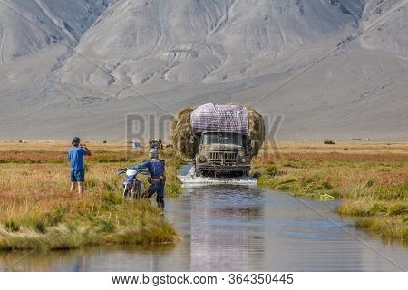 Altai, Mongolia - June 14, 2017: Truck Carrying Hay On A Road Covered With Water After A Flood. Alta
