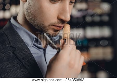 Sommelier Sniffs Smell Of Cork From Bottle Of Red Wine, Tests Drink