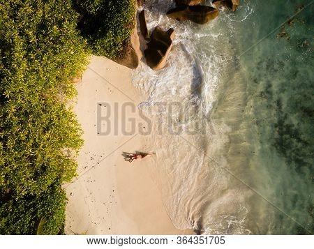 Beautiful woman in red bikini enjoys the tropical beach vacation. Birds eye view drone image from hi