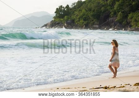 Blonde woman in beach dress enjoys the tropical sunset, looking at the sea, in Seychelles.