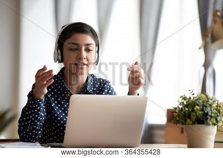Focused Young Indian Woman In Earphones Looking At Computer Screen.