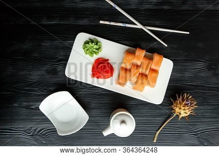 Appetizing Sushi Japanese Dish Of Salmon And Rice With Red And Green Pasta On A White Kitchen Board