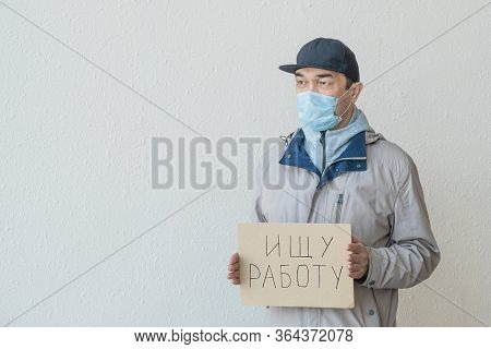 Asian Unemployed Adult Male In A Mask With Poster. Text In Russian: Looking For A Job. Unemployment,
