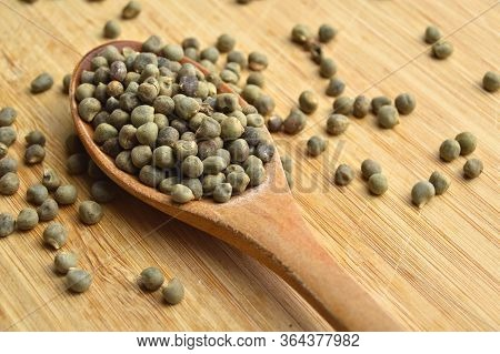 Many Dried Okra Seeds In Wooden Spoon, On Bamboo Cutting Board