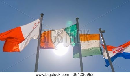 Diplomacy And International Affairs Concept. Colorful Flags Of Malta, Ireland, India, Croatia Flutte