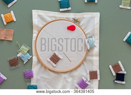 Embroidery Tools On Green Background With Wooden Embroidery Hoop, Needles, Needle Threader And Color