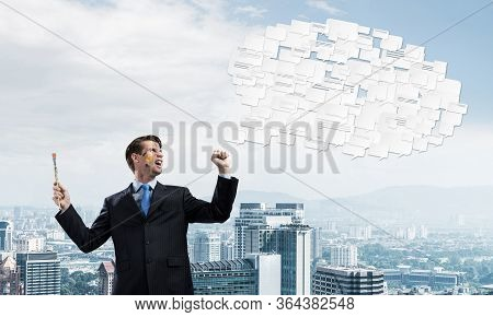 Conceptual Image Of Young And Successful Businessman In Black Suit Holding Paintbrush In Hand And Sm