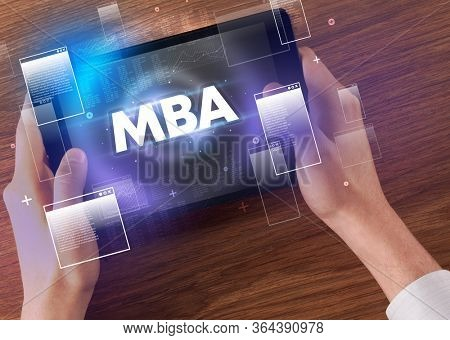 Close-up of a hand holding tablet with MBA abbreviation, modern technology concept