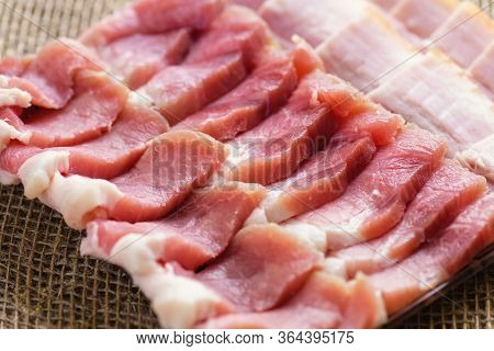 Fresh Cold Sliced Bacon On The Background Of Natural Linen Fabric. Raw Chopped Bacon For Cooking.