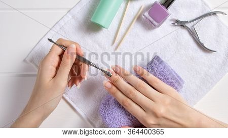 Manicure. Push Back The Cuticle With A Metal Pusher. Manicure Tools, Nail Polishes, Oil. Home Nail C