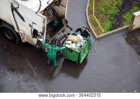 Garbage Removal In Residential Area, Garbage Men Loading Household Rubbish In Garbage Truck