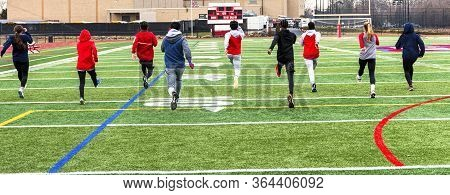 Rear View Of High School Track Team Of Boys And Girls Performing Warm Up Running Drils Side By Side
