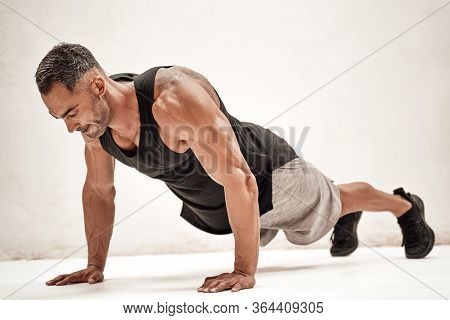 Masculine Sportsman Isolated On The White Background Wearing Sport Clothes Doing An Abdominal Bridge