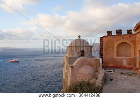 Panoramic View Of Ancient Church And Old Castle Ruins With Seaview And Ferry Boat In Oia Village On