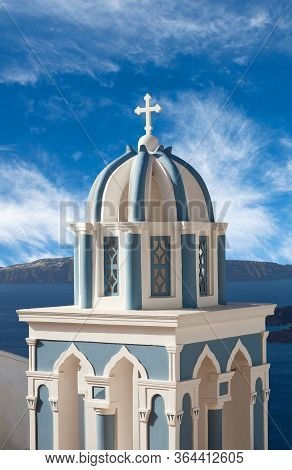 White And Blue Belfry Against Volcano Caldera On Santorini Island, Cyclades, Greece