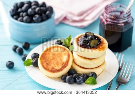 Syrniki Or Cottage Cheese Fritters With Blueberry Confiture On A Plate. Portion Of Syrniki. Sweet Br