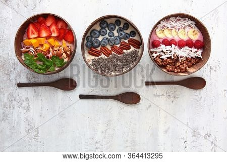 Balinese-style Breakfasts. Muesli With Yogurt And Berries In Plates Made Of Coconut Skin. Wooden Spo