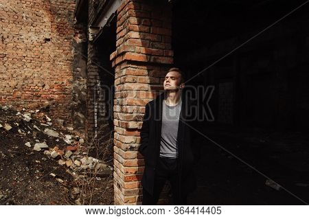 Young Man In The Coat Leaning Against The Wall In The Abandoned Buiding
