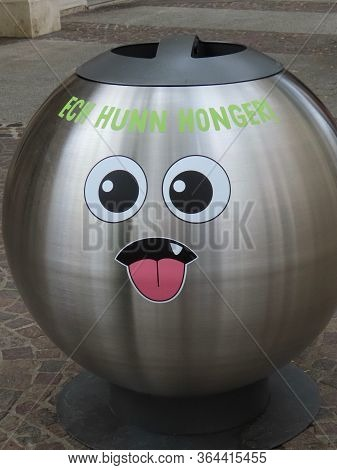 Trash Can In Luxembourg City Center. Round Polished Steel Bin With Stylish Face, Bulging Eyes, Pink
