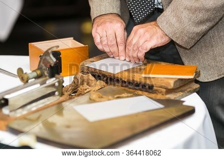 Mens Hands Twist Cuban Cigars Using Traditional Methods And Equipmentby Hand.