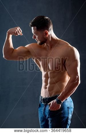 Athletic Man With Perfect Abs, Shoulders, Biceps, Triceps And Chest Showing His Biceps. Healthy Body
