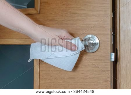 Hand Touches A Door Handle Through A Paper Serviette During A Coronavirus Epidemic. Transmission Of