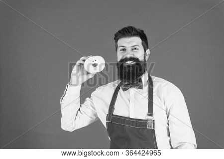 Bearded Well Groomed Man In Apron Selling Donuts. Donut Food. Baked Goods. Sweets And Cakes. Junk Fo