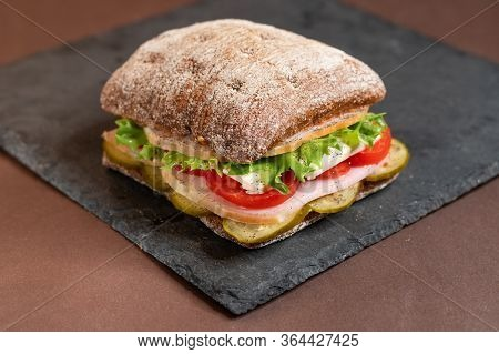 A Sandwich On A Tray. Sandwich With Meat And Vegetables On A Black Granite Stand. Special Square Rol