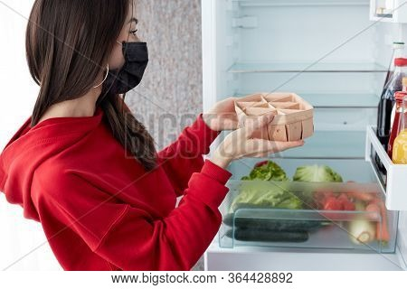 Close-up Of Young Woman Puts Food In The Fridge. Fresh Vegetables In The Fridge.