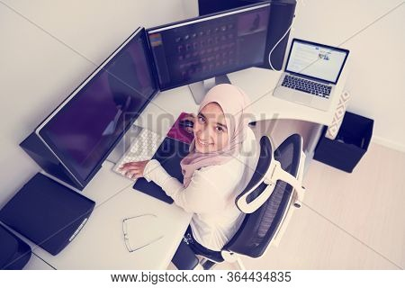 female Arabic creative professional  working at home office on desktop computer with dual screen monitor top view