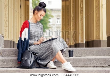Young College Girl Student Is Reading Book On Stairs. Young Female Student Is Sitting On The Outdoor