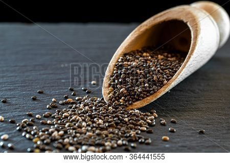 Pile Chia Flax Seeds Isolated On Black Food Background. Healthy Superfood In Wooden Spoon. Salvia Hi