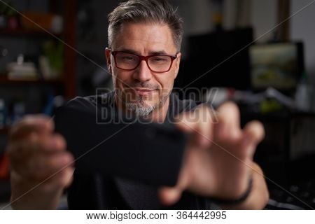 Man using smart phone at home sitting in armchair in cosy living room.