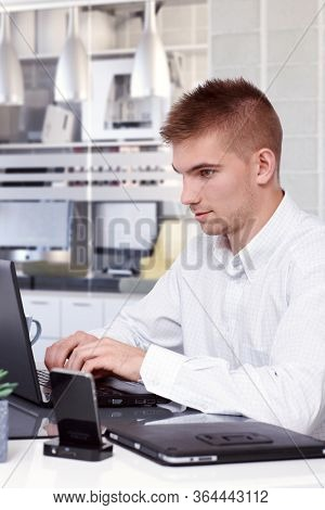 Young businessman working on laptop computer, typing on keyboard.