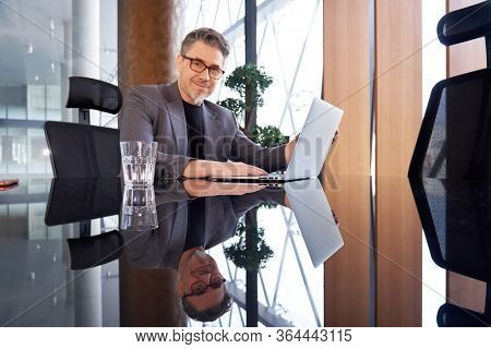 Confident happy older businessman in glasses wearing business casual sitting at office desk with laptop, thinking, listening, smiling.