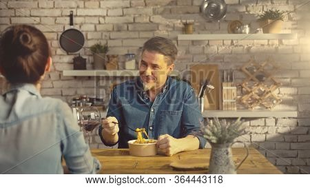 Casual white Couple eating take away pasta from food box at the table in kitchen at home.