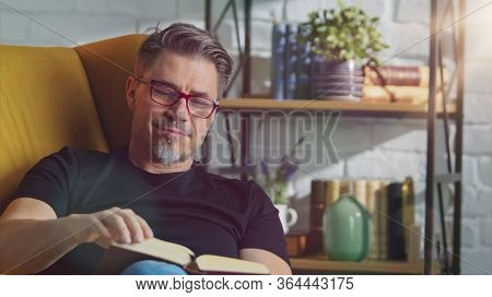 Older white man in glasses reading book at home sitting in armchair in cosy room.