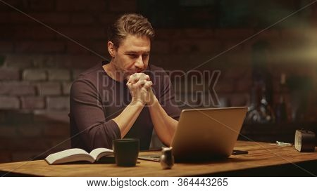 Older man tele working with laptop computer at home office in dark room, thinking, looking busy.