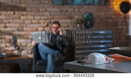 Covid-19 virus danger - Businessman working at safety of home office leaving virus protective mask on desk.