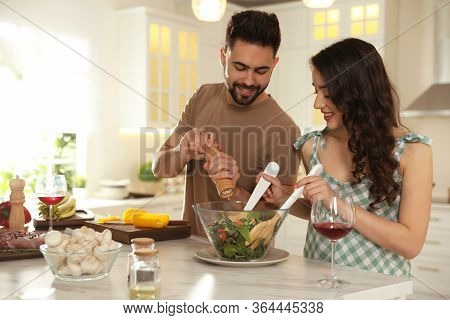 Lovely Young Couple Cooking Salad Together In Kitchen
