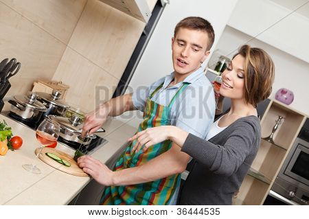 Man in striped apron cuts vegetables for dinner for his girlfriend in the modern comfortable kitchen