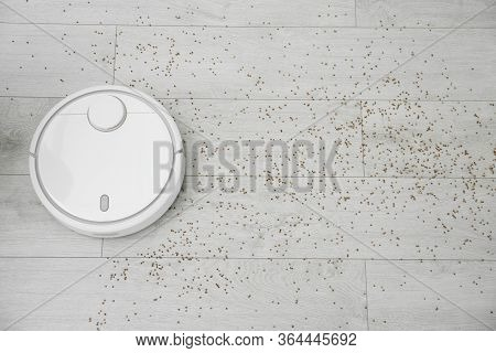 Removing Groats From Wooden Floor With Robotic Vacuum Cleaner At Home, Top View. Space For Text