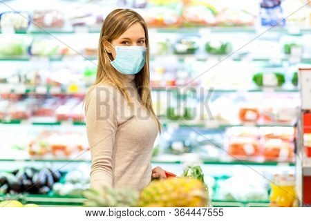 Woman shopping at the supermarket wearing a mask, coronavirus concept