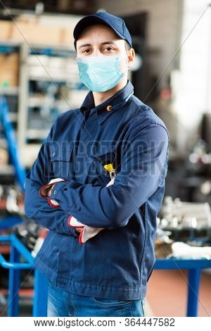 Young mechanic portrait wearing a mask