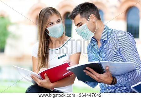 Couple of students talking together wearing a mask, coronavirus concept