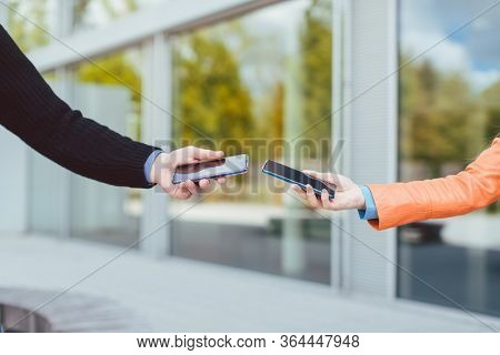 Woman and man with contact tracing app on their phones, only arms